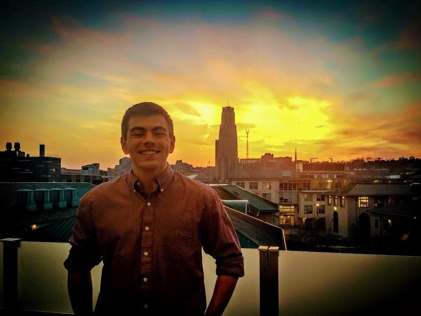 Scott Krulcik smiling in front of the Pittsburgh skyline